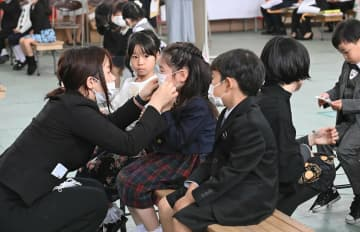 入学式後、先生にマスクを着けてもらう新1年生(8日午前11時28分、京都市伏見区・伏見住吉小)