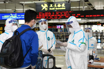 Customs workers check an inbound passenger's health information card in Shenzhen, South China's Guangdong province, on April 3, 2020. [Photo/Xinhua]