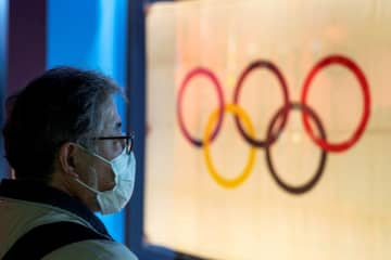 A man wearing a protective face mask, following an outbreak of the coronavirus, stands in front of The Tokyo Olympic flag 1964 at The Japan Olympics museum in Tokyo, Japan, Feb 26, 2020. [Photo/Agencies]