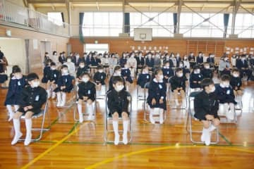 間隔を空けて座り、マスク姿で入学式に臨む船穂小1年生=9日午前10時7分
