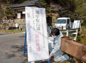 備中松山城のふいご峠駐車場で、入城の一時休止を知らせる看板を設置する市教委職員