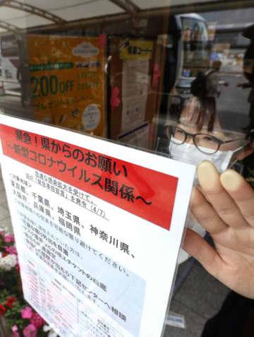 緊急事態宣言の対象地域との往来自粛などを呼び掛けるチラシ=9日午後、宮崎市錦町・宮崎駅バスセンター