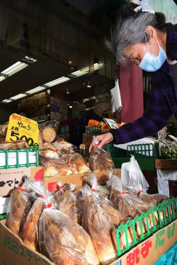 タケノコの売り場で品定めするマスク姿の客=横浜市南区
