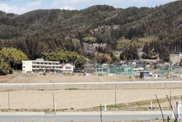 震災の津波で浸水した小友小校舎(左)。多くの家より低い土地にある=陸前高田市