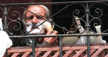 An elderly man applies shaving foam as he sits on his balcony in Sidon on Thursday during a countrywide lockdown to combat the spread of the coronavirus disease.