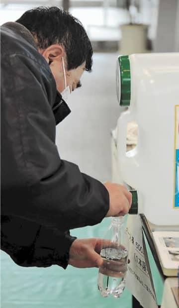 ペットボトルに次亜塩素酸水を入れる住民=9日、秋田県の横手市役所本庁舎