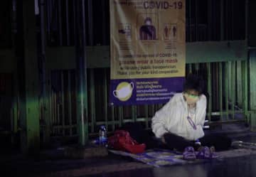 A homeless person with a face mask sits next to a street banner urging people to wear face masks to prevent the spread of Covid-19 virus outside Hua Lamphong railway station. Arnun Chonmahatrakool