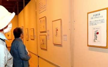 日本版の表紙絵を興味深そうに見つめる来場者=9日、鳥取市の県立博物館