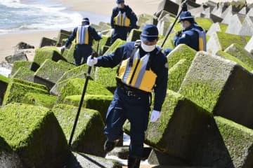 東日本大震災の行方不明者の手掛かりを求め、沿岸部を捜索する警察官=10日午前、福島県いわき市