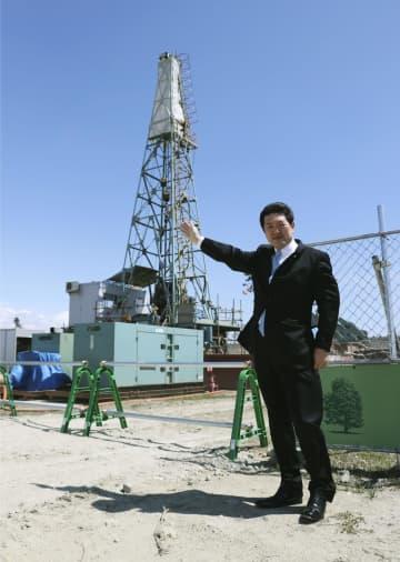 建設現場に立ち、温泉掘削機(後方)を紹介する「仙台reborn」の深松努代表取締役=10日午前、仙台市
