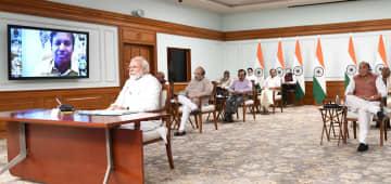 閣僚と等間隔で座り、テレビ会議に臨むモディ首相(左)=8日、ニューデリーで(インド政府提供)