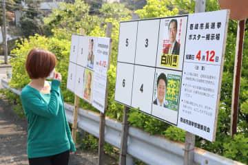 選挙ポスターの掲示板を眺めるマスク姿の市民=壱岐市郷ノ浦町