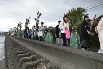 鍋や釜をもした冠をかぶった少女たちが琵琶湖岸を歩く「鍋冠祭」(2018年5月3日、滋賀県米原市世継)