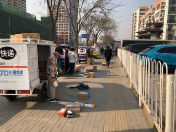 北京の団地の外でずらりと並ぶ宅急便の三輪車。中には入れないため、電話をして取りにきてもらう(2020年4月9日、筆者撮影)