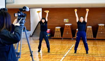 家庭でできる中学生向けの運動を紹介した番組を収録する関係者=24日午後、伊予市上吾川の郡中小学校
