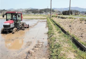 水田を代かきする梅津さん。崩れたのり面は土がむき出しで、道路は路肩が一部削り取られている