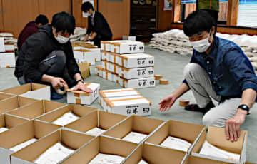 新入生への応援便として米やマスクを箱詰めする同窓会員=16日、鳥取市賀露町北4丁目