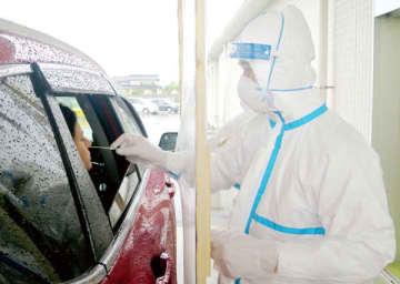 車の窓越しにPCR検査をする医師。1分ほどで検査は終わった=16日午後、加須市北小浜の「西山救急クリニック」
