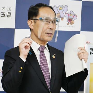石川遼選手から寄贈されるフェースシールドグラスを試着する大野元裕知事=18日午後、県庁