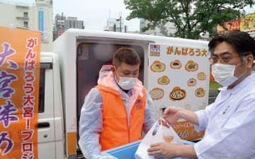 注文を受けた料理を専用の宅配車両に積み込む料理人ら=16日午後、大宮駅東口