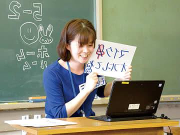 テレビ会議システムを使った「朝の会」で、児童たちに言葉をかける担任教諭=越谷市立大袋小学校