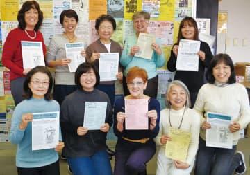紙面を手に笑顔のメンバー(2月撮影)