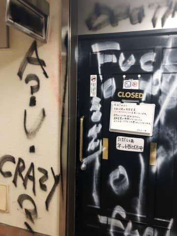 入り口ドアや周りの壁に店をののしる言葉を落書きされたバー「来月きっと潰れます」=7日、大阪市(同店提供)