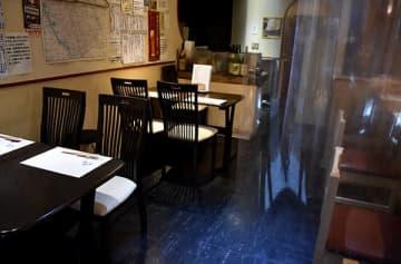 カウンター席を透明シートで仕切り、テーブル席は対面禁止にして安全対策を図っている居酒屋=18日午後5時ごろ、さいたま市南区