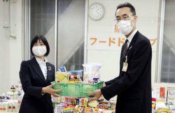 山崎達也福祉部長(右)から食材の贈呈を受ける埼玉フードパントリーネットワークの草場澄江代表=21日、県庁