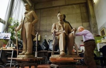 中村晋也さんの手で完成した像の原型。右から堀孝之、高見弥一=鹿児島市常盤1丁目