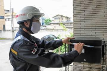 マスクをポストに投函する郵便配達員