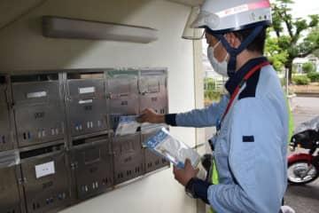布マスクを各家庭に配達する宮崎中央郵便局の配達員=23日午前、宮崎市日ノ出町