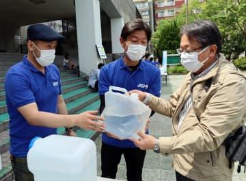 長崎青年会議所のメンバーから次亜塩素酸水を受け取る市民(右)=長崎市民会館前