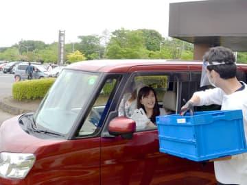 ドライブスルーで商品を受け渡しする客とスタッフ=23日、久喜市鷲宮総合支所