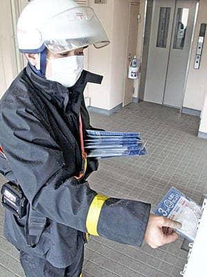 政府支給の布マスクをポストに入れる配達員=23日午前、福島市