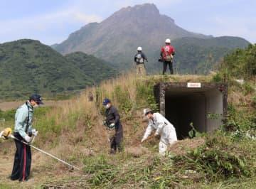 「いのりの日」を前に、雲仙岳災害記念碑周辺を清掃する参加者。後方は平成新山=島原市北上木場町