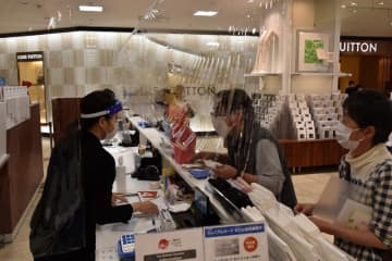 ビニールシート越しに会計する買い物客とフェイスシールド姿の従業員=23日午後、そごう千葉店