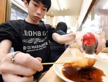 ボトルから串カツに直接ソースをかける方法に切り替えた=22日、大阪市浪速区の串かつだるま通天閣店