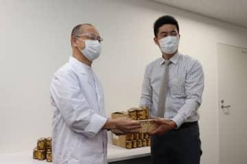 藤森勝也院長(左)に「ナッツスター」を手渡す八米代表の高橋敦志さん=阿賀野市