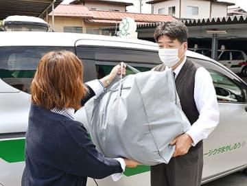 希望時間に合わせ、うるしやまタクシーの運転手(右)が衣類を受け取りに訪れるクリーニングサービス