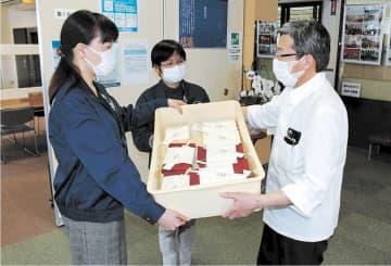 井上さん(右)から弁当を受け取る商議所の職員