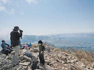 磐梯山山頂から絶景を楽しむ登山者=24日午前