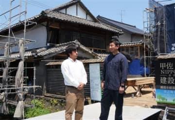 「NIPPONIAホテル甲佐(仮称)」建設現場の前で談笑する、パレットの大滝祐輔さん(左)と米原賢一さん=甲佐町