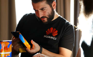 A Huawei employee demonstrates the features of the Huawei Mate XS device, during a media event in London, Britain, February 18, 2020. [Photo/Agencies]