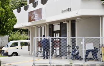 男女2人が切りつけられた喫茶店周辺を調べる捜査員ら=25日午前、那覇市
