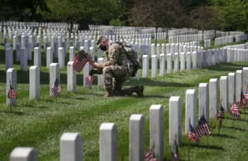 A U.S. Army Old Guard member carries small American flags to place in front of the headstones of U.S. service members buried at Arlington National Cemetery in Arlington, Virginia, U.S., May 21, 2020. (photo credit: TOM BRENNER/REUTERS)