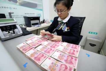 A clerk counts cash at a bank in Huaibei, Anhui province. [Photo provided to China Daily]