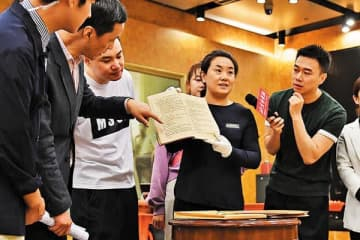 Chen Li (center), an associate researcher of the theater museum of Beijing People's Art Theater, displays a manuscript to visitors on May 18. [Photo provided to China Daily]