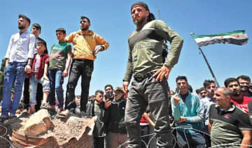 Syrians gather outside a Turkish army base near Idlib to demand the Turks fulfill their side of a truce agreement and allow them to return to their homes.