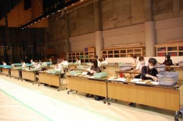 【舞台の上に机を並べ、郵送による申請書の開封作業にあたる職員ら=鈴鹿市神戸1丁目の市民会館で】